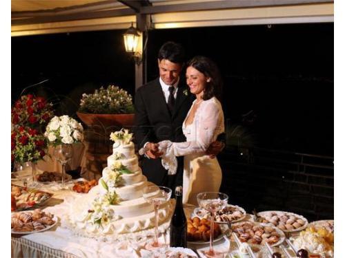 Taglio della torta tra un gustoso buffet di dolci