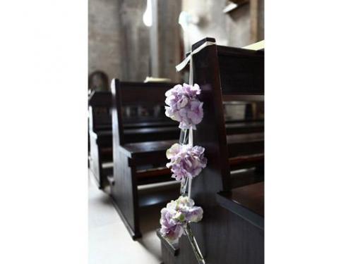 Sfere di orchidee a cascata sui banchi della chiesa