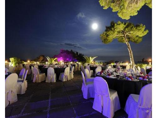 Allestimento dei tavoli in terrazza per ricevimento serale