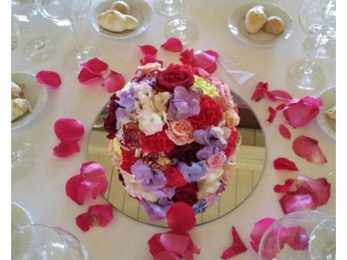 Sfera multicolore e petali rosa sparsi sul tavolo