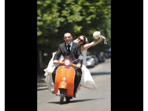 Gli sposi, allegri e pimpanti, che vanno via in vespa